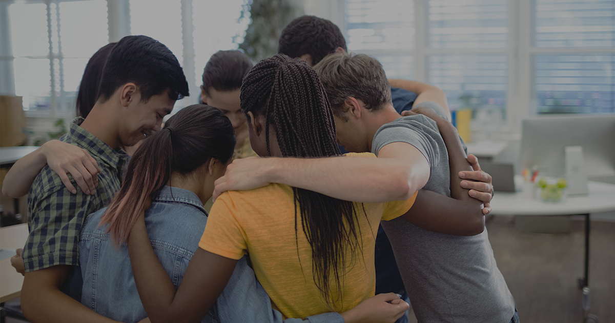 A diverse group of people in an encouraging huddle