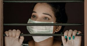 Women with facemask staring out behind bars